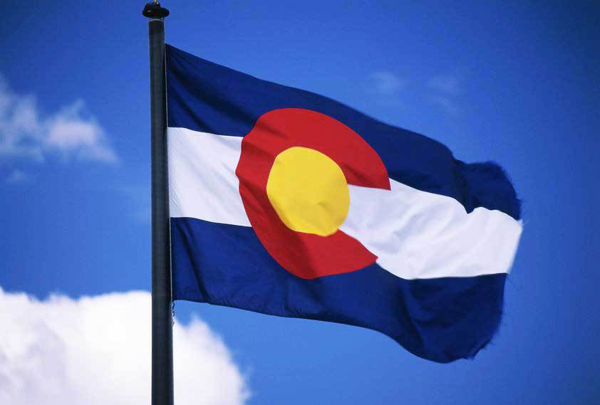 a colorado flag flows in the wind | erie co HOA management